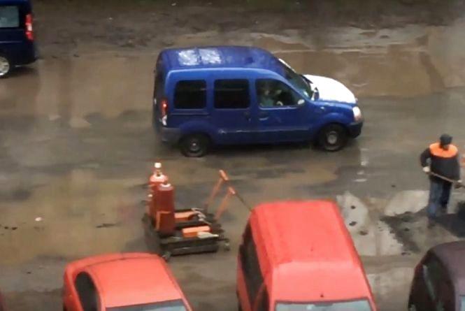 Асфальтом в калюжу: на Зарічанській під час дощу латали дорогу (ВІДЕО)
