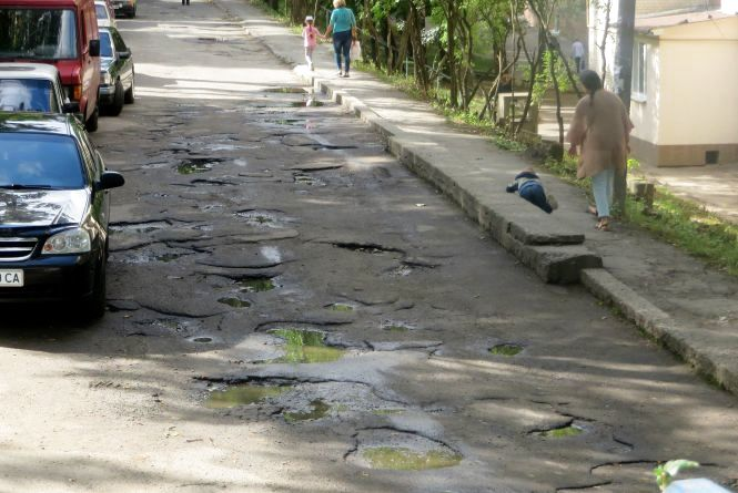 """Ями по кісточки. Мешканці Тернопільської скаржаться,  що дощ """"з'їдає"""" асфальт біля будинку"""